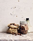 A paper bag of hazelnuts, a storage jar of muesli and a bottle of almond milk