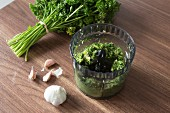 Garlic, parsley and butter being chopped in a vegetable hacker