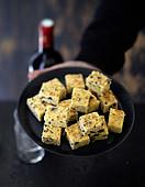 Polentaschnittchen mit schwarzen Oliven und Parmesan