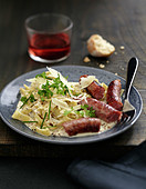 Fresh tagliatelles with chipolatas sausages and black pepper