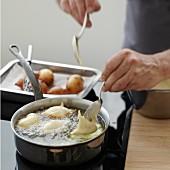 Deep-frying spoons full of Croustillons batter in hot oil