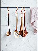 Aufgehängte Küchenutensilien: Schöpfkelle, Pfannenwender, Holzlöffel, Sieblöffel