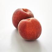 Zwei Pfirsiche vor weißem Hintergrund