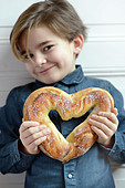 Child holding a heart-shaped bread