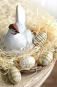 Decorated Easter eggs and a china hen in a raffia nest