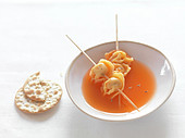 Beef tortellinis brochettes with carrot and cumin broth