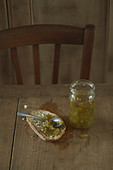 Jar of green tomato jam and spread on a slice of bread