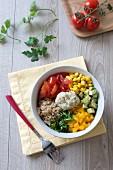 Tomato, avocado, sweet corn, mango and aubergine caviar Buddha bowl