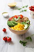 Orientalische Buddha Bowl mit Kirschtomaten, Mango, Kichererbsen, Avocado, Griess und Gurke