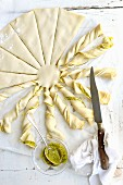 Twisting slices of the filo pastry with the pesto to shape the sun beams