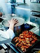 Koch in einer Restaurantküche gibt lebende Flusskrebse ins kochende Wasser