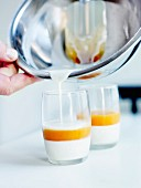 Pouring a layer of vanilla-flavored liquid cream on the apricot pulp in the glasses