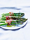 Bundles of green asparagus with anchovies, smoked bacon and thyme