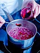 Natürlichen Rosenextrakt zur Mischung aus Zuckerwasser, Erdbeeraroma und Farbstoff hinzufügen