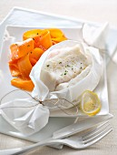 Lemon-flavored cod papillote and thin strips of carrots with honey
