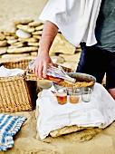 Mann am Strand schenkt spritzigen Apfelsaft ein