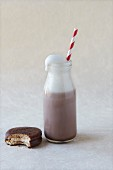 Bottle of chocolate milk with a straw and a bitten biscuit
