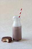 Flasche Schokoladenmilch mit Strohhalm und angebissenem Keks