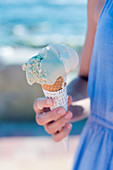 Person holding an ice cream cone outdoors