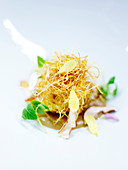 Fried leek nest with flower petals and treacle