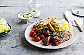 Grilled steak, potatoes, roasted bunch of tomatoes and mushrooms