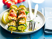 Salmon, cod, courgette, cherry tomato and pepper brochettes with pink and black pepper
