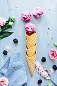 Komposition mit Eistüten, Kugeln Schokoladen-Brombeer-Eiscreme, Blüten und Löffel mit Zucker