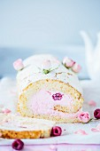 Rolled sponge cake garnished with raspberries and rose