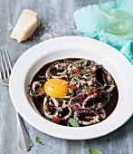 Nage-Suppe mit Tintenfisch in der Sepiatinte, gegrillter Sobresada, Eidotter, Parmesan und Basilikum