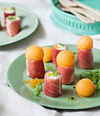 Raw ham and fromage frais rolls with melon balls