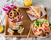 Onion rings, BLT sandwich, Miami beach salad and pieces of tuna-avocado-vegetable club-sandwich