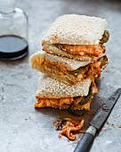 Tempeh, kimchi and mayonnaise sesame bread sandwich