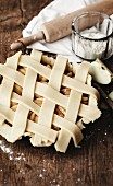 Covering the apple pie with criss-cross strips of uncooked pastry