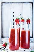 Drei Flaschen Wassermelonen-Smoothie mit Erdbeeren