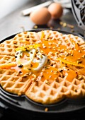 Preparing waffles with orange coulis, confit orange rinds and pistachios