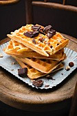 Pile of Brussels waffles, squares of dark chocolate and hazelnuts