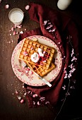 Pile of plain Brussels waffles with red berry coulis, cream and pink pralines
