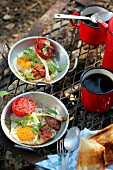 Tin plat of fried egg and tomatoes, cup of coffee for a picnic