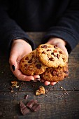 Child with a handful of chocolate chip and pecan cookies