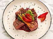 Duck breast with black and golden sesame seeds, cranberry sauce, plums and spring vegetables