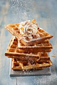 Sprinkling icing sugar onto the waffles from Brussels with whipped cream and almonds