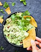 Dipping a Mexican tortilla in a bowl of guacamole