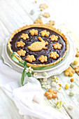 Easter chocolate tart decorated with flower and rabbit-shaped shortbreads