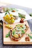 Belegtes Brot mit Auberginenkaviar, weissen Trauben, Fourme d'Ambert-Käse und Walnüssen