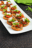 Häppchen mit Parmesan, Pesto und eingelegten Tomaten