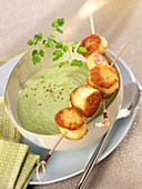 Cream of pea soup with quenelle brochettes