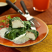 Cod wrapped in spinach leaves and seedy mustard creamy sauce