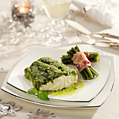 Piece of cod in pesto sauce, bundle of green beans wrapped in bacon