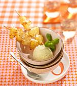 Pineapple and coconut brochettes, scoop of vanilla ice cream