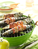 Mackerels with thyme and bay leaves wrapped in smoked bacon on the barbecue